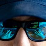 In der Sonnenbrille eines jungen Mannes mit schwarzem Hoodie und Basecap spiegelt sich ein Laptop mit grüner Schrift auf schwarzem Hintergrund. Man sieht seine Hände auf der Tastatur und einen gruseligen Sticker daneben.