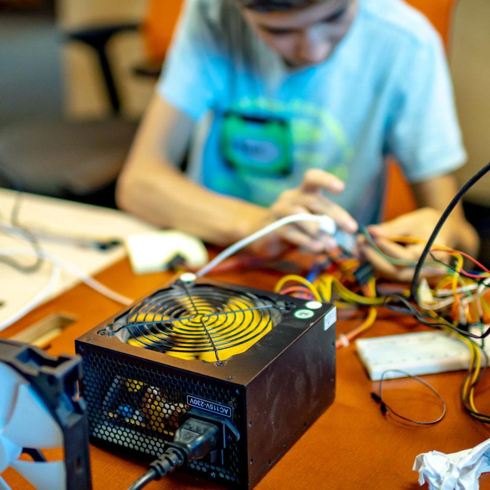Junger Entwickler baut mit Lüftern und Wassertank an einer Klimaanlage