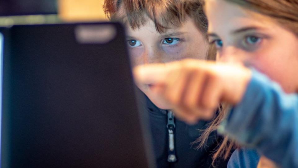 Zwei Kinder schauen konzentriert gemeinsam auf einen Laptop-Monitor